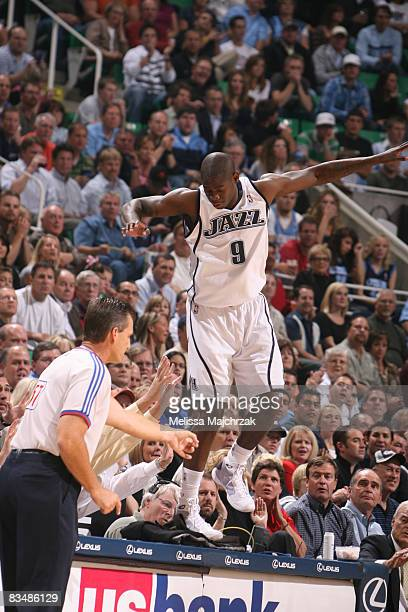 Ronnie Brewer of the Utah Jazz goes for the save and ends up on the stats table against the Denver Nuggets at the season opener at EnergySolutions...