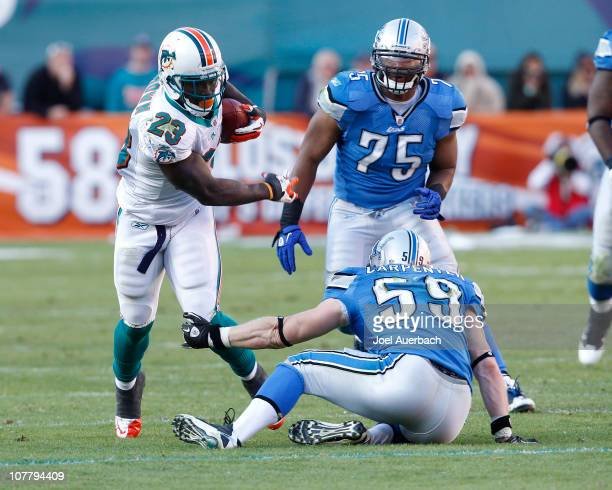 Ronnie Brown of the Miami Dolphins eludes an attempted tackle by Bobby Carpenter of the Detroit Lions on December 26 2010 at Sun Life Stadium in...
