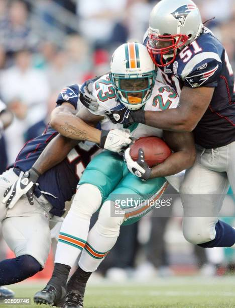 Ronnie Brown of the Miami Dolphins is stopped by Pat Chung and Jerod Mayo of the New England Patriots on November 8 2009 at Gillette Stadium in...
