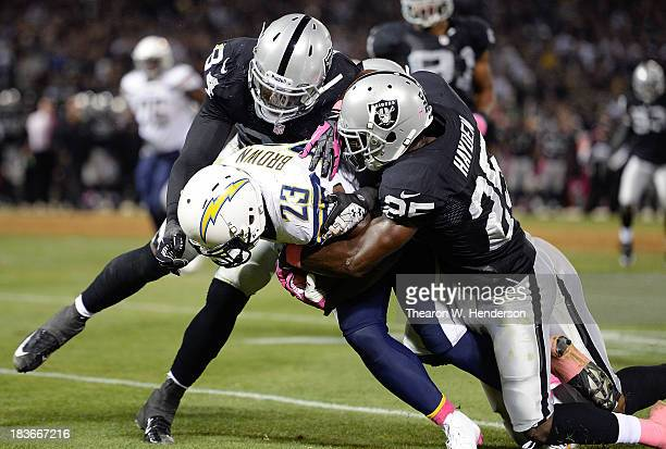Ronnie Brown of the San Diego Chargers gets tackled by DJ Hayden and Kevin Burnett of the Oakland Raiders during the third quarter at Oco Coliseum on...