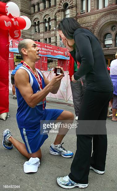 PROPOSAL 1 09/27/09 Ronnie Garcia of Markham goes on bended knee after finishing the Toronto Waterfront Marathon near old city hall to propose...