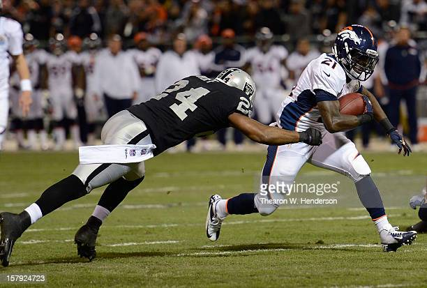 Ronnie Hillman of the Denver Broncos attempts to avoid the tackle of Michael Huff fo the Oakland Raiders in the first quarter at OaklandAlameda...