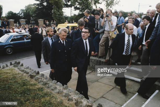 Ronnie Kray center is escorted by prison officers and past the waiting media as he attends the funeral of his mother Violet at Chingford Mount...