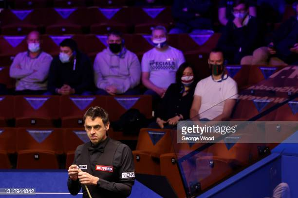 Ronnie O'Sullivan chalks his cue as spectators wearing face masks watch on during the Betfred World Snooker Championship Round One match between...