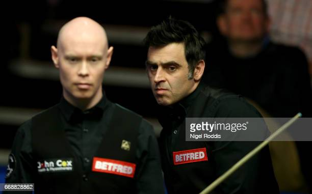 Ronnie O'Sullivan of England and Gary Wilson of England during their first round match on day one of the World Championship Snooker at the Crucible...