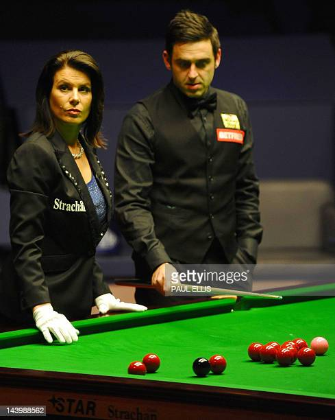 Ronnie O'Sullivan of England and referee Michaela Tabb reposition the balls after a foul during the second session of the World Championship Snooker...