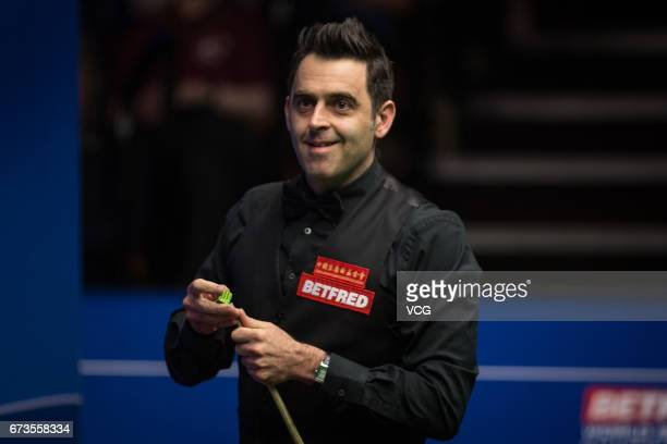 Ronnie O'Sullivan of England chalks the cue during his quarter final match against Ding Junhui of China on day twelve of Betfred World Championship...