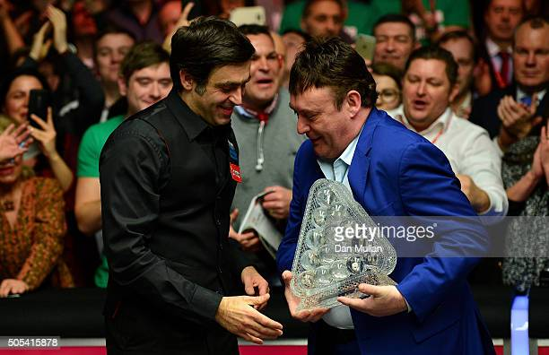 Ronnie O'Sullivan of England is presented with The Dafabet Masters Trophy by former player Jimmy White of England during Day Eight of The Dafabet...
