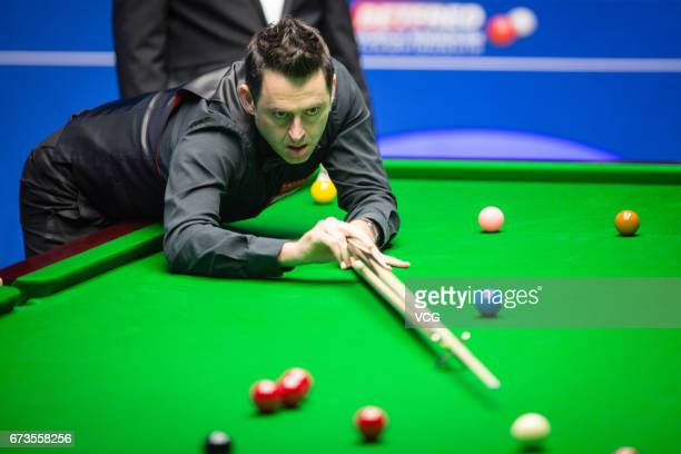 Ronnie O'Sullivan of England plays a shot during his quarter final match against Ding Junhui of China on day twelve of Betfred World Championship...