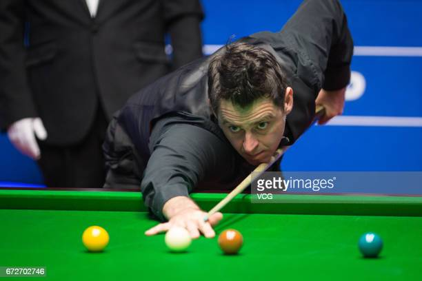 Ronnie O'Sullivan of England plays a shot during his quarter-finals match against Ding Junhui of China on day eleven of Betfred World Championship...