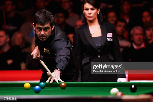 Ronnie O'Sullivan of England plays a shot in his match against Mark Allen of Northern Ireland watched by referee Michaela Tabb in Round One of The...