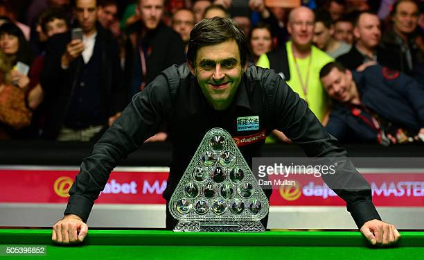 Ronnie O'Sullivan of England poses with the Dafabet Masters Trophy after defeating Barry Hawkins of England in the final match during Day Eight of...