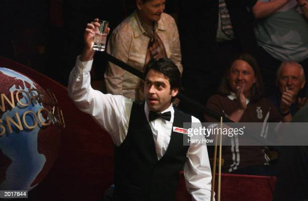 Ronnie O'Sullivan of England raises a glass to the cheering crowd after scoring a maximum 147 break during the first round of the Embassy World...
