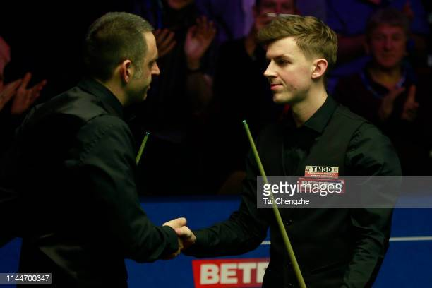 Ronnie O'Sullivan of England shakes hands with James Cahill of England after their first round match against during day four of the 2019 Betfred...