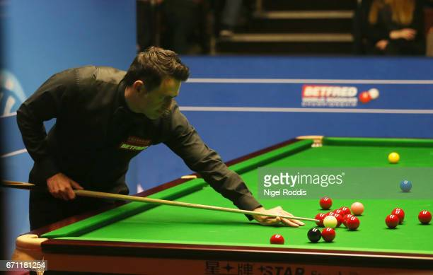 Ronnie O'Sullivan plays a shot against Shaun Murphy during their second round match of the World Snooker Championship on day 7 at Crucible Theatre at...