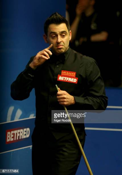 Ronnie O'Sullivan reacts after playing a shot against Shaun Murphy during their second round match of the World Snooker Championship on day 7 at...