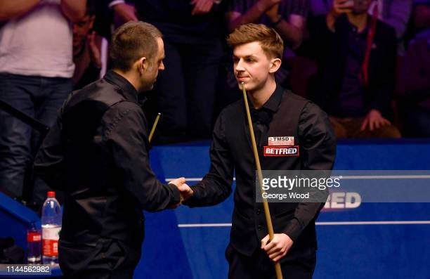 Ronnie O'Sullivan shakes hands with James Cahill following Cahill's win in the opening round of the world snooker championship at Crucible Theatre on...