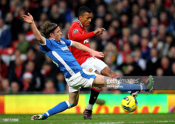 Ronnie Stam of Wigan Athletic challenges Nani of Manchester United during the Barclays Premier League match between Manchester United and Wigan...