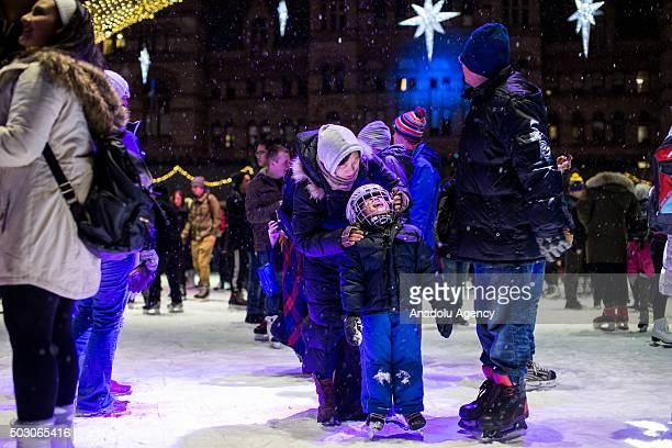 Ronnie Wang centre attempts to catch snow flakes with parents Vivian and Victor right on the ice rink as revelers await the countdown to midnight at...