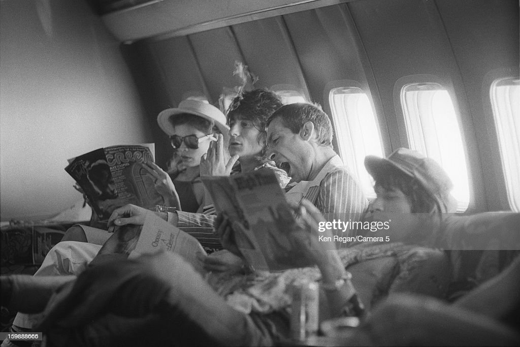 Ronnie Wood, Charlie Watts and Keith Richards of the Rolling Stones with Bianca Jagger are photographed reading on their plane in 1975 in Kansas City, Kansas.