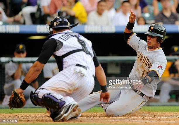 Ronny Cedeno of the Pittsburgh Pirates slides safely into home before the tag of catcher Yorvit Torrealba of the Colorado Rockies as Cedeno scored on...