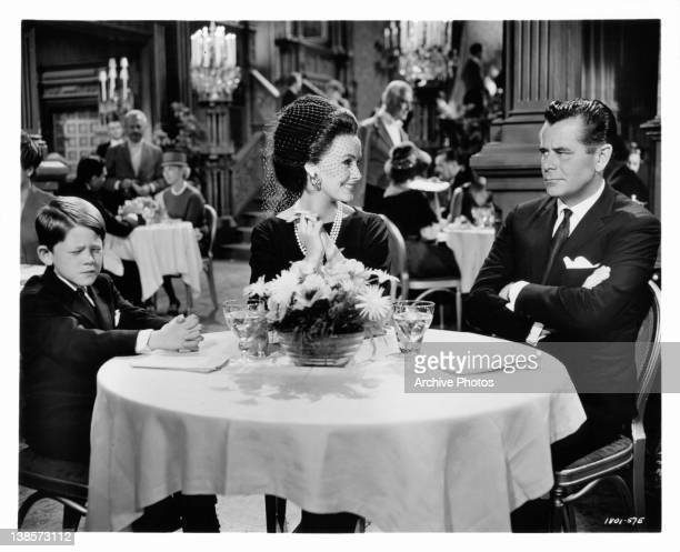 Ronny Howard sits displeased with Glenn Ford choice of dinner guest, Dina Merrill in a scene from the film 'The Courtship Of Eddie's Father', 1963.