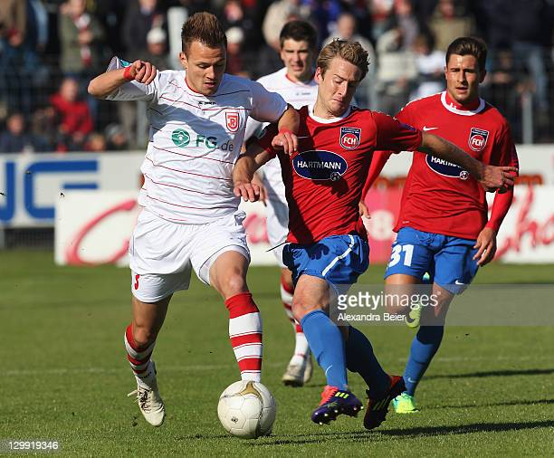 Ronny Philp of Regensburg fights for the ball with Christian Sauter of Heidenheim during the third league match between Jahn Regensburg and 1. FC...