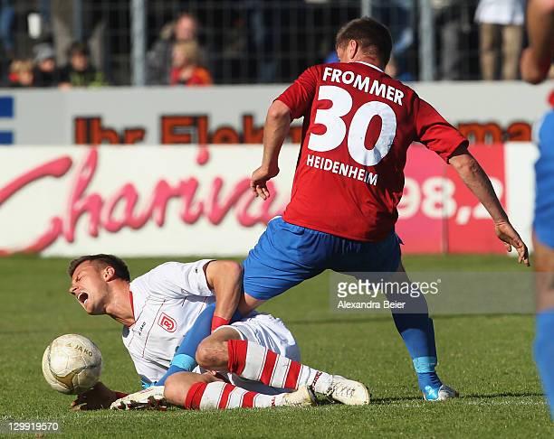 Ronny Philp of Regensburg is challenged by Nico Frommer of Heidenheim during the third league match between Jahn Regensburg and 1. FC Heidenheim at...
