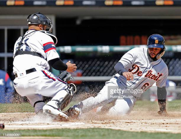 Ronny Rodriguez of the Detroit Tigers scores against Welington Castillo of the Chicago White Sox following a double off the bat of Grayson Greiner...