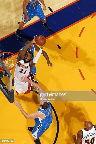 Ronny Turiaf of the Golden State Warriors grabs a rebound against Darius Songaila and Hilton Armstrong of the New Orleans Hornets during a preseason...