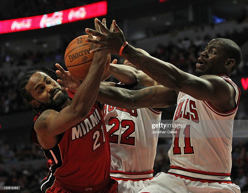 Ronny Turiaf #21 of the Miami Heat battles for a rebound with Taj Gibson #22 and Ronnie Brewer #11 of the Chicago Bulls at the United Center on April 12, 2012 in Chicago, Illinois.