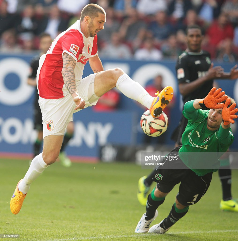 Ron-Robert Zieler of Hannover 96 saves a goal attempt from Sascha Moelders of FC Augsburg during the Bundesliga match between FC Augsburg and Hannover 96 at SGL Arena on May 16, 2015 in Augsburg, Germany.