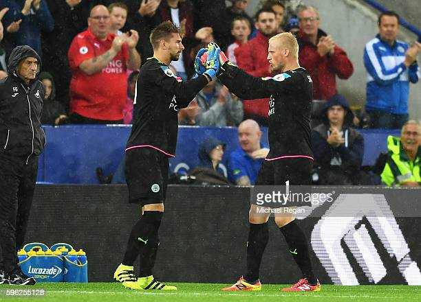 RonRobert Zieler of Leicester City high fives Kasper Schmeichel of Leicester City after being subbed for him during the Premier League match between...