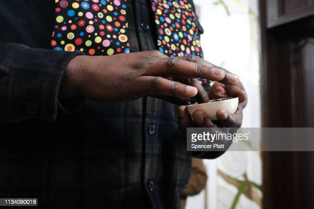 Roody Chatelain, a worshipper at the Church of the Village, administers a glitter ash cross on a forehead during a service at the historic church...