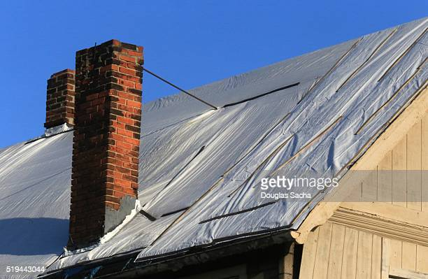 roof covering on a dilapidated house - tarpaulin stock pictures, royalty-free photos & images
