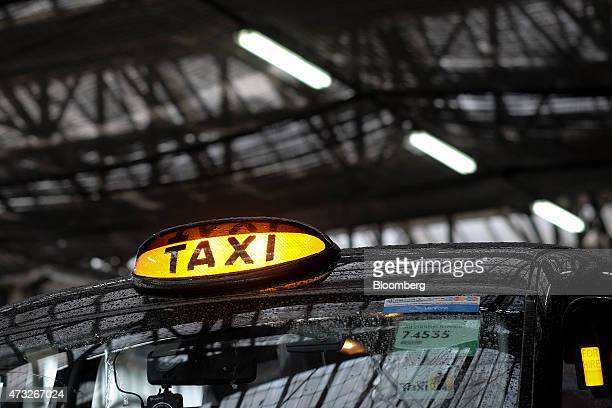 A roof light sits illuminated on a London taxi cab as it awaits a fare from a taxi rank outside Waterloo railway station in London UK on Thursday May...
