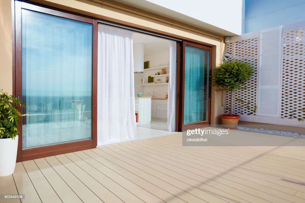 roof top patio with open space kitchen, sliding doors and decking on upper floor : Stock Photo