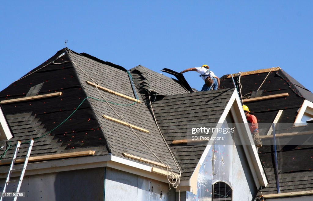 Roof Workers on top of house with blue sky : Stock Photo
