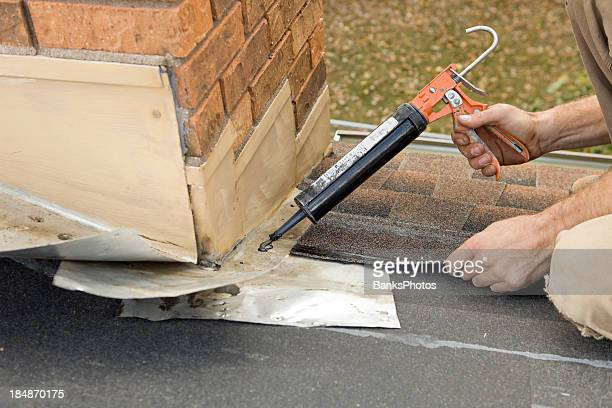 Roofer Applying Caulk to House Chimney Flashing
