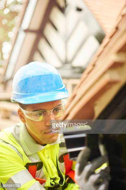 roofer fixing gutters - black glove stock pictures, royalty-free photos & images