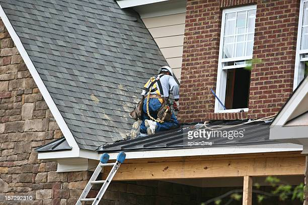 A roofer fixing the roof of a brick house