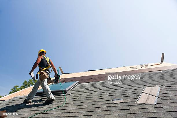 Roofer installing flashing on skylight