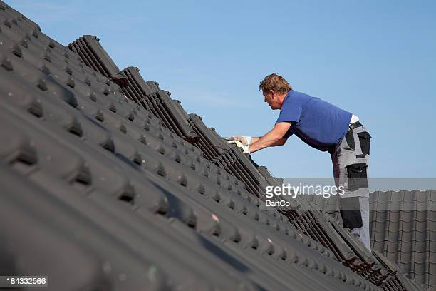 Roofer is working hard on a roof.