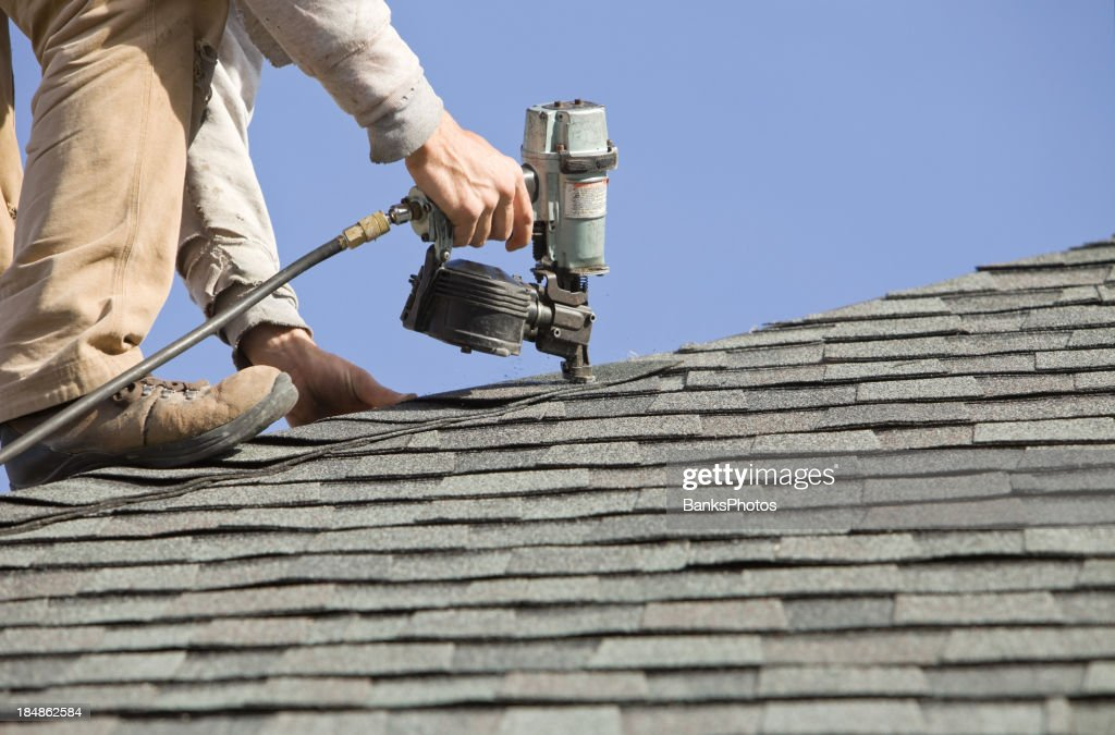 Roofer Nailing Cap Shingle to a New House Roof : Stock Photo