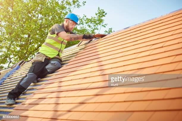roofer on the roof - solo un uomo di età media foto e immagini stock