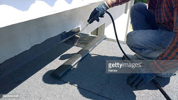 roofer preparing part of bitumen roofing felt roll for melting by gas heater torch flame - membrane stock photos and pictures