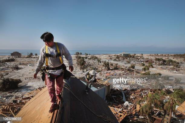 A roofer replaces the roof on a town home after it was damaged by Hurricane Michael on October 16 2018 in Mexico Beach Florida The neighborhood which...