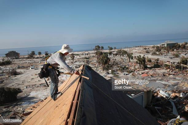 A roofer replaces the roof on a townhome after it was damaged by Hurricane Michael on October 16 2018 in Mexico Beach Florida The neighborhood which...
