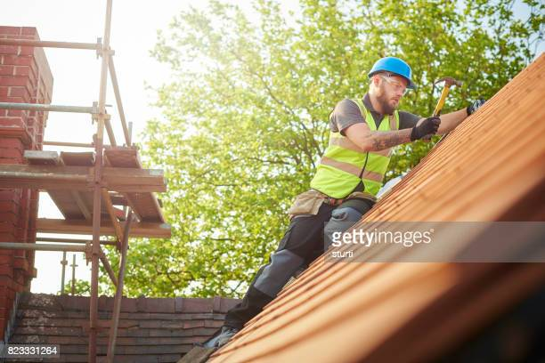 roofer replacing the old tiles - roof stock pictures, royalty-free photos & images