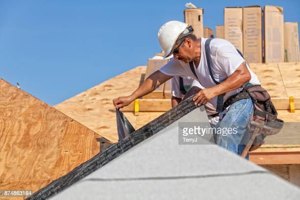 roofer tears off protective cover of underlayment on a new roof - membrane stock photos and pictures